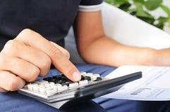 Ung man som kontrollerar en räkning, en budget eller en lönelista royaltyfria foton