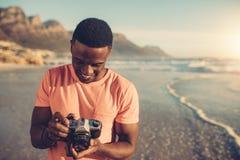 Ung man som kontrollerar foto i digital kamera Fotografering för Bildbyråer
