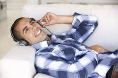 Ung man som kopplar av att lyssna till musik hemma Arkivfoto