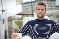 Ung man som kopplar av med hans kaffe på en Cafe Royaltyfria Bilder