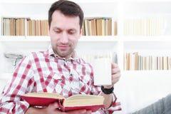 Ung man som kopplar av på soffaläseboken och tycker om kaffe royaltyfri fotografi