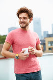 Ung man som kopplar av på takterrass med koppen kaffe Arkivbild