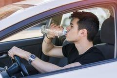 Ung man som kör bilen och dricksvatten från Royaltyfri Fotografi