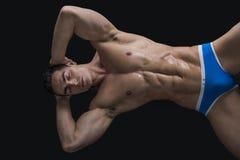 Ung man som lägger på golvet med den nakna muskulösa kroppen Arkivbilder
