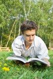 Ung man som läser en tidskrift i parken Royaltyfri Fotografi