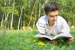 Ung man som läser en tidskrift i parken Fotografering för Bildbyråer