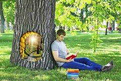 Ung man som läser ett boksammanträde på benägenheten för grönt gräs på ett träd i parkera Royaltyfria Bilder