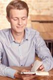 Ung man som läser hans anmärkningar i kafé Arkivfoton