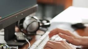 Ung man som långsamt skriver på tangentbordet stock video