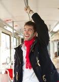 Ung man som ler att resa med kollektivtrafik Royaltyfria Bilder