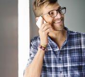 Ung man som ler det talande Smartphone begreppet arkivfoto