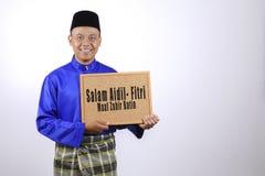 Ung man som ler med den svart tavlan för den Eid Fitr eller Eid Adha celeben Arkivfoton