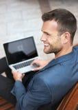 Ung man som ler med hans bärbar dator Royaltyfria Bilder