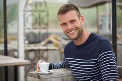 Ung man som ler med hans kaffe på en strandCafe Royaltyfri Foto