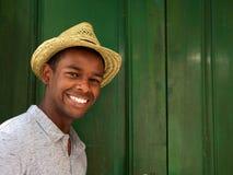 Ung man som ler med hatten på grön bakgrund arkivbilder