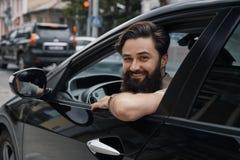 Ung man som ler, medan köra en bil fotografering för bildbyråer
