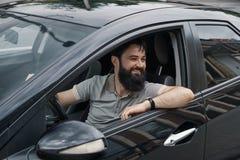 Ung man som ler, medan köra en bil royaltyfria foton