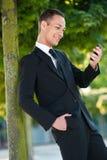Ung man som ler på hans telefon i Park Royaltyfri Fotografi
