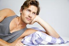 Ung man som ligger, i att dagdrömma för säng Royaltyfri Bild