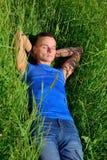 Ung man som ligger i gräset på en solig dag fotografering för bildbyråer