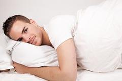 Ung man som ligger i säng royaltyfria bilder