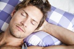 Ung man som ligger i säng Royaltyfri Bild