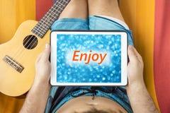 Ung man som ligger på en hängmatta med minnestavlaapparaten som ser suddig blå bakgrund med ord & x22; Enjoy& x22; skriftligt på  arkivfoto