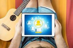 Ung man som ligger på en hängmatta som besöker en social nätverkswebsite med minnestavlaapparaten Royaltyfri Foto
