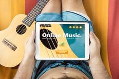 Ung man som ligger på en hängmatta som besöker online-wi för en musikwebsite Royaltyfria Bilder