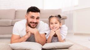 Ung man som ligger på golv med hans förtjusande dotter arkivbilder