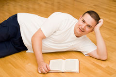 Ung man som ligger på golvet med boken arkivbild