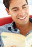 Ung man som läser en bok Arkivfoton