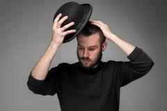 Ung man som lyfter hans hatt i respekt och royaltyfri foto