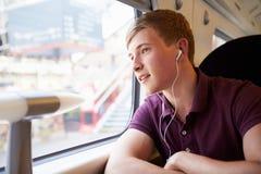 Ung man som lyssnar till musik på drevresa Royaltyfri Bild