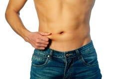 Ung man som mäter fett på buken Arkivbilder