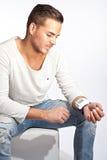 Ung man som mäter hans blodtryck royaltyfria bilder