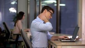 Ung man som masserar den stelfrusna halsen, effekter av stillasittande arbete, ryggrads- problem, h?lsa arkivfoton