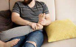 Ung man som masserar hans fot för vän` s arkivbild