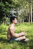 Ung man som mediterar eller gör utomhus- yogaövning Fotografering för Bildbyråer