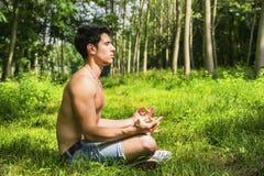 Ung man som mediterar eller gör utomhus- yoga Arkivbilder