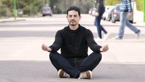 Ung man som mediterar i mitt av gatan lager videofilmer
