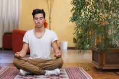 Ung man som mediterar på hans vardagsrumgolv Arkivfoton