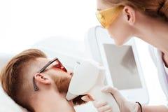 Ung man som mottar laser-hudomsorg på framsidan som isoleras på vit Royaltyfri Fotografi
