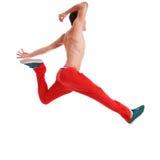 Ung man som mycket poserar i en höjdhoppdansflyttning Arkivbild