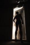 Ung man som nästan står den öppna dörren Arkivfoto