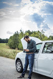 Ung man som ner använder hans mobiltelefon bredvid en bruten bil Royaltyfria Foton