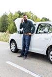 Ung man som ner använder hans mobiltelefon bredvid en bruten bil Royaltyfri Foto