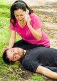 Ung man som ner ligger med det medicinska nödläget, kvinnasammanträde av hans sida som kallar för hjälp, utomhus miljö Arkivbild