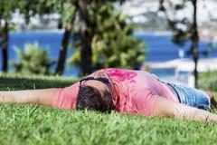Ung man som ner ligger på ett nytt grönt gräs i en tropisk trädgård Royaltyfria Bilder