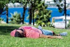 Ung man som ner ligger på ett nytt grönt gräs i en tropisk trädgård Arkivfoton